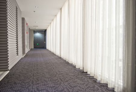 carpet flooring: A long hotel corridor perspective with doors. Editorial