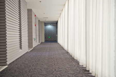 A long hotel corridor perspective with doors.