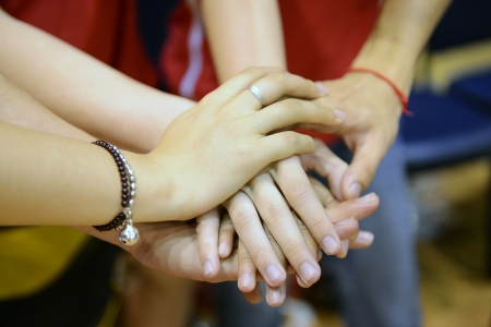 solidarity: team of friends showing unity with their hands together Stock Photo