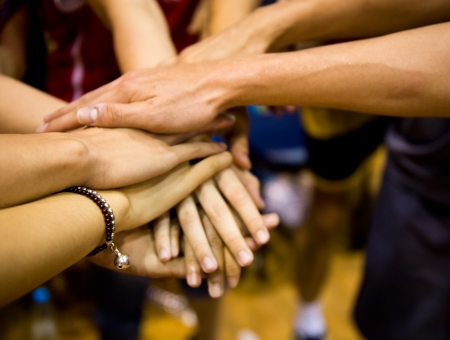team of friends showing unity with their hands together Imagens