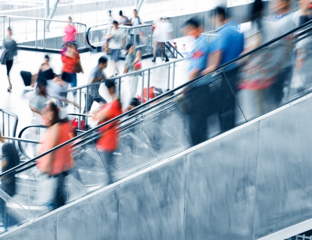 moving down: People rush on escalator motion blurred. Stock Photo