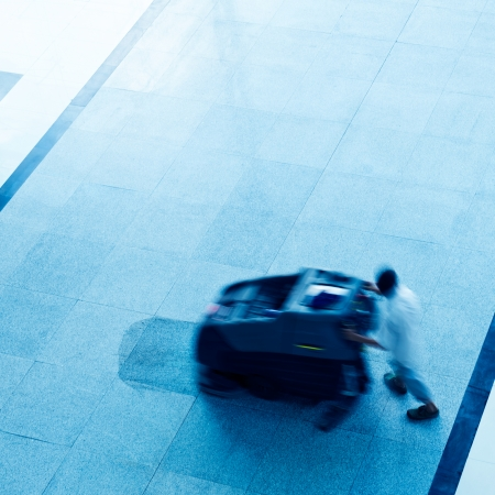 People cleaning floor with machine. blur motion