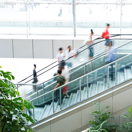 hurry up: People rush on escalator motion blurred. Stock Photo