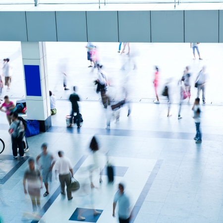 Pohled shora davu lidí v pohybu na moderní budovy.