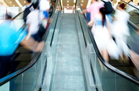 People rush on escalator motion blurred. photo