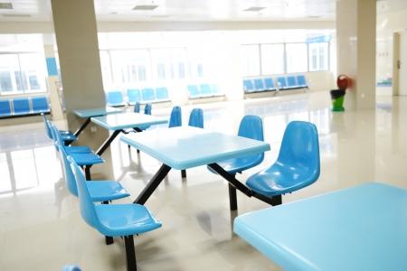 comedor escolar: Limpie cafetería de la escuela con muchos asientos vacíos y mesas. Editorial