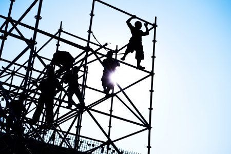 Construction workers working on scaffolding photo