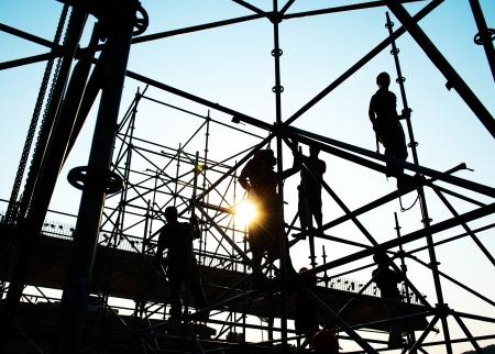Werknemers in de bouw werken op steigers