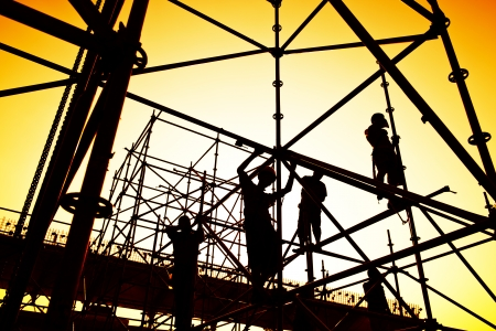formwork: Construction workers working on scaffolding
