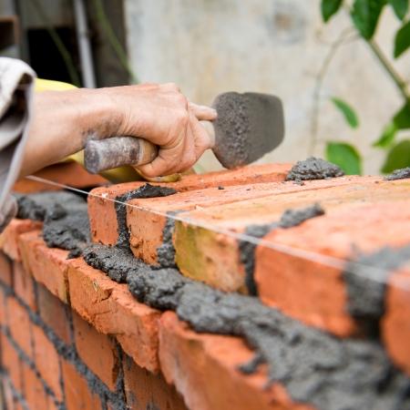 brick mason: builder laying bricks in site.