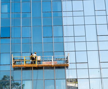 Werknemers van steeplejack wassen van ramen van het moderne gebouw.