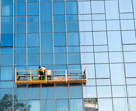 Workers of steeplejack washing windows of the modern building. Stock Photo