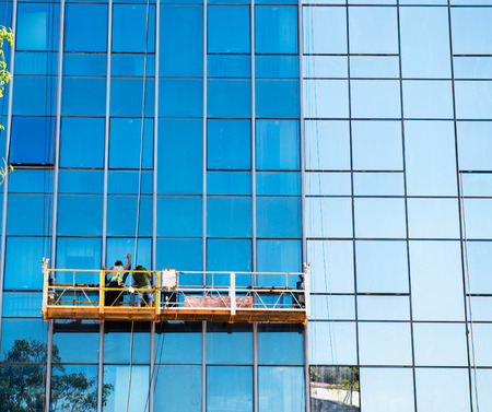 high rise: Workers of steeplejack washing windows of the modern building. Stock Photo