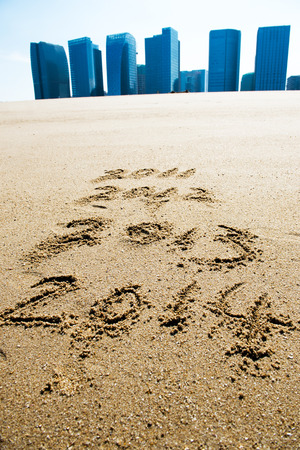 digits 2013 and 2014 on the sand seashore  photo