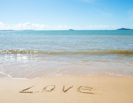 The word LOVE written on sand. photo