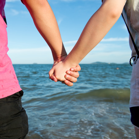 Summer couple holding hands in front of the sea.