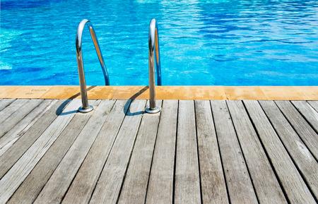 convés: Piscina com escada e deck de madeira no hotel. Imagens
