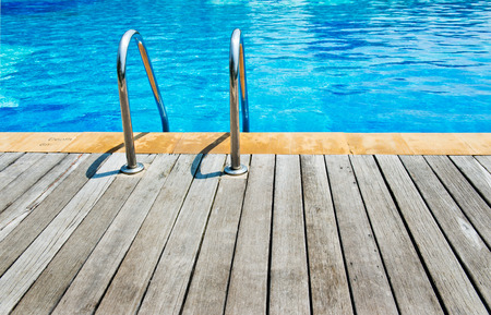 edges: Swimming pool with stair and wooden deck at hotel.