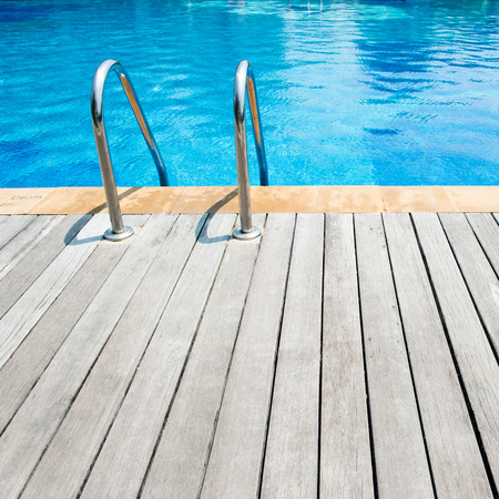 pool deck: Swimming pool with stair and wooden deck at hotel.