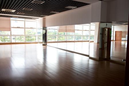 Leere Tanzsaal mit Holzboden und Spiegel.