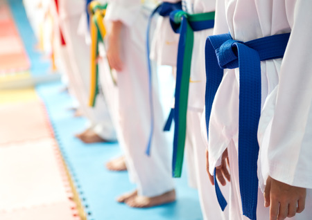 belts: People in martial arts training exercising Taekwondo.