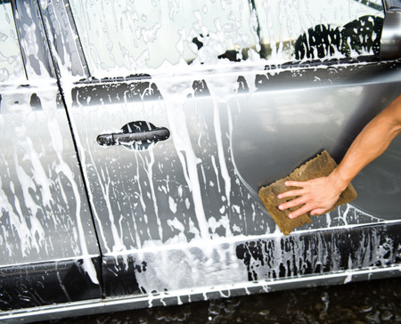 washing car: hand hold sponge over the car for washing. Stock Photo