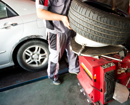 auto lift: mechanic hands with tool repairing the car at garage. Stock Photo