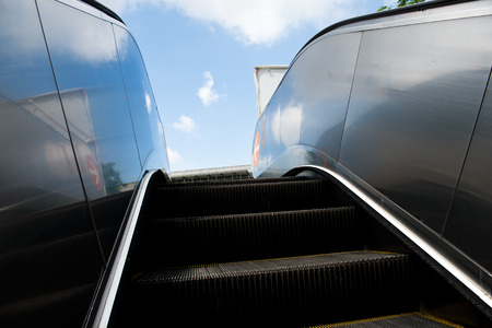 Wide angled view to perspective escalators stairway with background of blue sky. photo