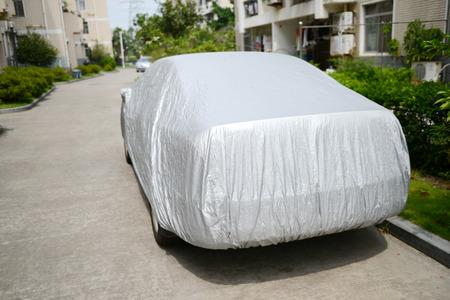 Une voiture avec une feuille de couverture pour la protection de la lumière du soleil. Banque d'images