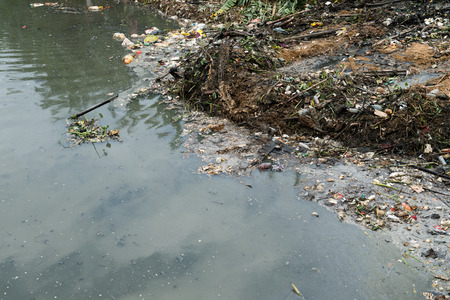 repulsive: Water pollution in river with trash.