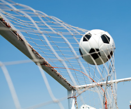 soccer net: soccer ball in goal. isolated on blue sky background
