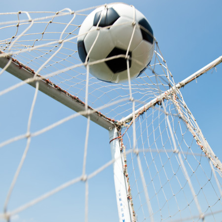 soccer ball in goal. isolated on blue sky background photo