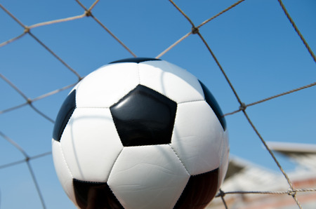 soccer ball in goal. isolated on blue sky background