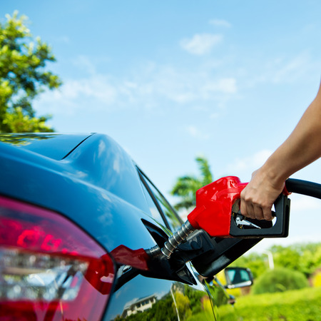 Hand refilling the car with fuel. Stock Photo - 33756944