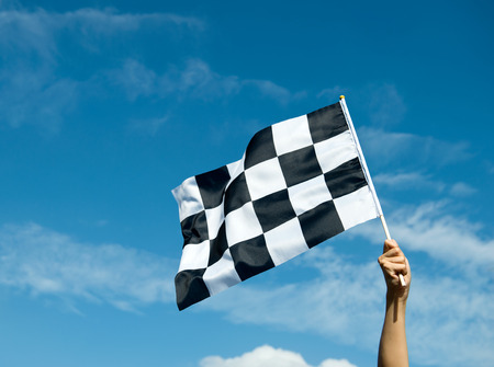 finish: checkered race flag in hand.