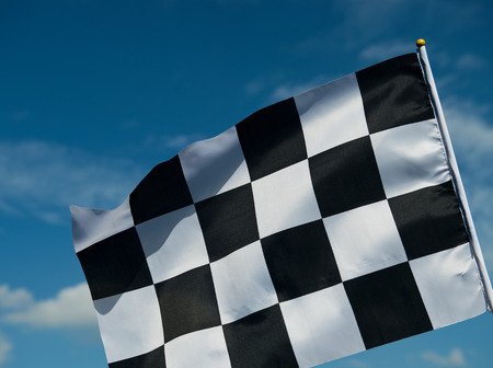 checkered race flag waving on blue sky. photo