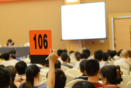 People holding auction paddle to buy from auction. Banque d'images
