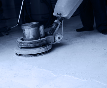 office cleanup: People cleaning floor with machine.