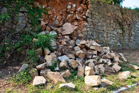 rubble: Broken stone wall after earthquake.