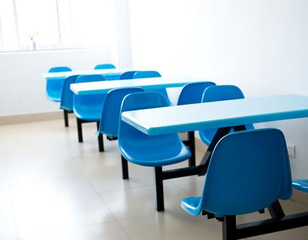 comedor escolar: Cafetería limpia con asientos y mesas vacías.