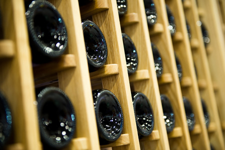 intoxicant: Group of red wine bottles stacked on wooden racks.