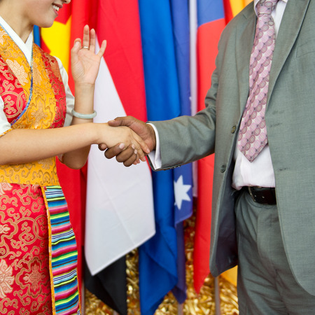 African businessmans hand shaking white Chinese womans hand. photo