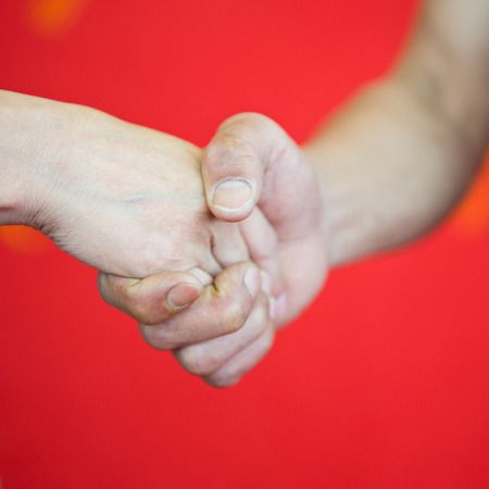 aisa: man and woman hand shaking isolated on red background. Stock Photo