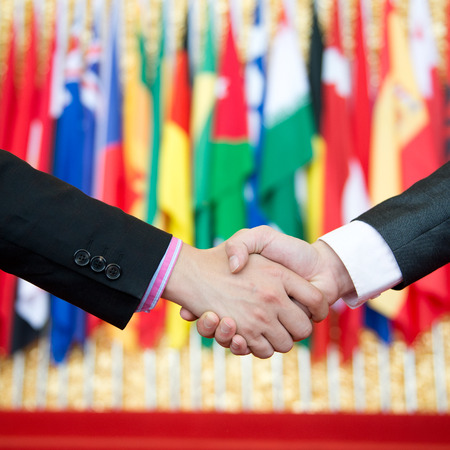 international business agreement: Businessmen shaking hands in front of the multi - national flag.    international business