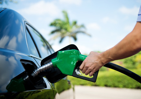 Hand refilling the car with fuel.