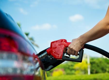 gasolinera: Rellenar a mano el coche con combustible. Foto de archivo