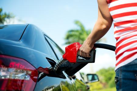 bomba de gasolina: Rellenar a mano el coche con combustible. Foto de archivo