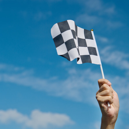 winning race: checkered race flag in hand.