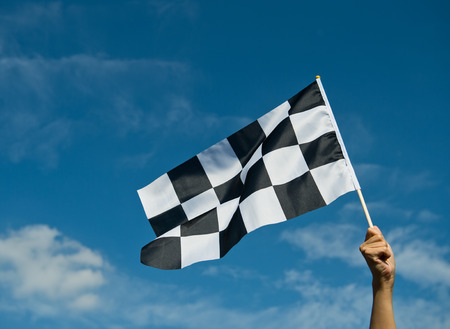 formula one racing: checkered race flag in hand.