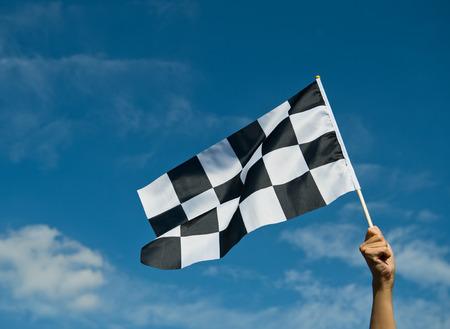 geruite ras vlag in de hand.